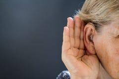 Donna anziana con perdita dell'udito su fondo grigio Relativo all'età immagine stock