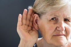 Donna anziana con perdita dell'udito su fondo grigio Relativo all'età fotografie stock libere da diritti