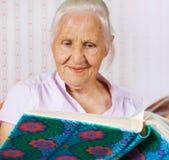 Donna anziana con un album della famiglia Fotografie Stock Libere da Diritti