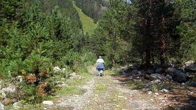 Donna anziana con una canna che cammina lungo la strada rocciosa video d archivio