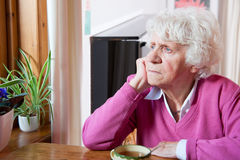 Donna anziana depressa che si siede alla tabella Immagini Stock Libere da Diritti