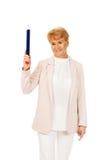 Donna anziana di sorriso che indica su con la penna del hege Fotografia Stock Libera da Diritti