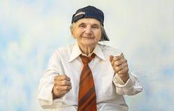 Donna anziana divertente che sostiene qualcosa immagine stock