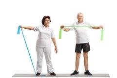 Donna anziana e un uomo anziano che risolve con gli elastici Immagini Stock Libere da Diritti