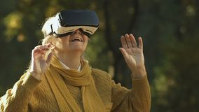 Donna anziana facendo uso della cuffia avricolare di VR, mondo virtuale d'esplorazione, spettacolo moderno archivi video
