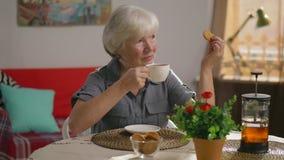 Donna anziana felice in abbigliamento casual che beve tè e che mangia i biscotti video d archivio