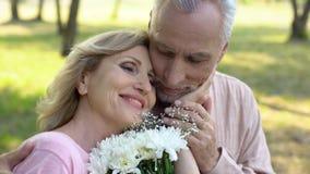 Donna anziana felice che tiene i fiori, segnanti fronte maschio, amore maturo, romanzesco immagine stock libera da diritti