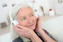 Donna anziana felice con le cuffie fotografia stock