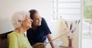 Donna anziana felice e nipote di Gap di generazioni che prendono Selfie Fotografia Stock