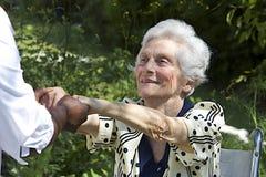 Donna anziana felice in sedia a rotelle Immagine Stock
