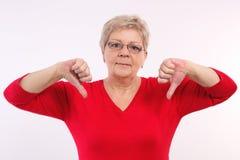 Donna anziana infelice che mostra i pollici giù, emozioni negative nella vecchiaia Fotografia Stock