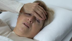 Donna anziana malata che tocca fronte con tremare mano, febbre durante l'influenza, virus video d archivio