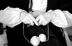 donna anziana mentre tricottando lana con due fili di lana Fotografia Stock Libera da Diritti