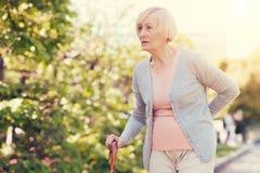 Donna anziana piacevole che la tiene indietro Fotografia Stock Libera da Diritti