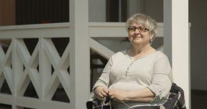 Donna anziana senior che tricotta aria aperta di seduta e sorridente al portico della Camera del colpo di Terrasse sulla macchina stock footage