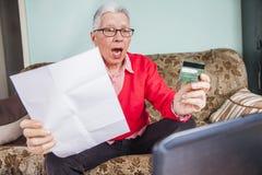 Donna anziana senior colpita dalla sua fattura di carta di credito Immagini Stock