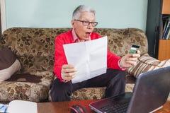 Donna anziana senior colpita dalla sua fattura di carta di credito Fotografie Stock Libere da Diritti