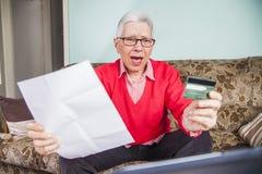 Donna anziana senior colpita dalla sua fattura di carta di credito Fotografia Stock Libera da Diritti