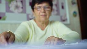 Donna anziana senior Defocused in occhiali che controlla i costi delle spese quotidiane a casa archivi video
