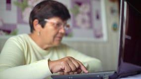 Donna anziana senior in occhiali che praticano il surfing Internet sul computer portatile a casa con spazio libero e lo spazio de video d archivio