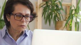 Donna anziana sicura che lavora al progetto online con il computer portatile nello spazio ufficio stock footage