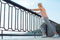 Donna anziana snella che allunga sul ponte Fotografia Stock Libera da Diritti