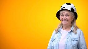 Donna anziana sorridente che porta il cappello divertente di calcio, modello per l'annuncio, scommessa di sport fotografia stock libera da diritti