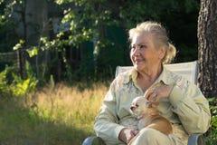 Donna anziana sorridente con la sua chihuahua sorridente immagine stock