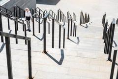 Donna anziana stanca che scala i grandi punti con le rotaie all'aperto Immagine Stock Libera da Diritti