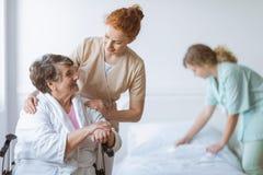 Donna anziana sulla sedia a rotelle nella casa di cura fotografia stock libera da diritti