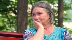 Donna anziana triste nel parco video d archivio