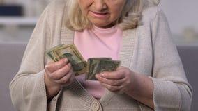 Donna anziana turbata che conta le banconote del dollaro, pagamento basso di pensionamento, pensione stock footage
