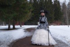 Donna anziana in un vestito gotico in un cappello con un ombrello nero sulla natura nell'inverno immagine stock