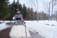 Donna anziana in un vestito gotico in un cappello con un ombrello nero sulla natura nell'inverno immagine stock libera da diritti