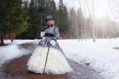 Donna anziana in un vestito gotico in un cappello con un ombrello nero sulla natura nell'inverno fotografia stock libera da diritti