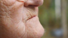 Donna anziana in vetri che mettono pillola bianca nella sua bocca Chiuda sul movimento lento di vista laterale archivi video