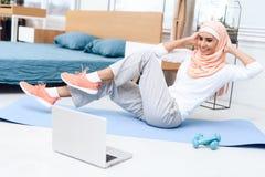 Donna araba che fa ginnastica nella camera da letto immagine stock libera da diritti