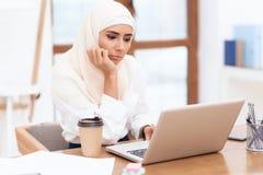 Donna araba che indossa una seduta del foulard stanca sul lavoro immagini stock libere da diritti