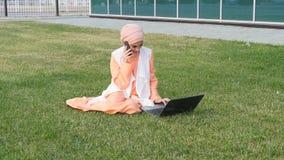 Donna araba di affari sul telefono cellulare in un parco stock footage