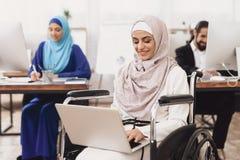 Donna araba disabile in sedia a rotelle che funziona nell'ufficio La donna sta lavorando al computer portatile immagine stock