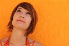 Donna in arancio che osserva in su Fotografia Stock