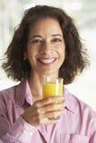 donna arancione centrale bevente invecchiata della spremuta fresca Immagine Stock