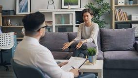Donna arrabbiata che esprime le emozioni durante il consiglio della sessione con lo psicologo stock footage