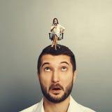Donna arrabbiata che si siede sull'uomo stupito Fotografia Stock