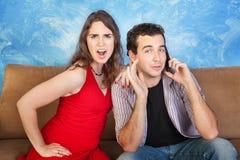 Donna arrabbiata con l'uomo sul telefono Fotografie Stock