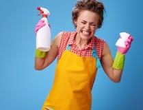 Donna arrabbiata con la spugna della cucina e bottiglia del detersivo sul blu fotografie stock