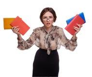 Donna arrabbiata dell'insegnante in vetri con i libri isolati sulla parte posteriore di bianco Immagini Stock Libere da Diritti