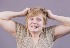 Donna arrabbiata molto emozionale con i denti dell'oro su un fondo grigio Fotografia Stock