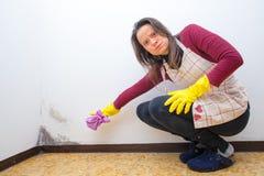 Donna arrabbiata perché trova la muffa sulle pareti della casa immagini stock