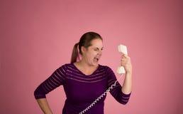 Donna arrabbiata sul telefono legato con corde Fotografie Stock Libere da Diritti